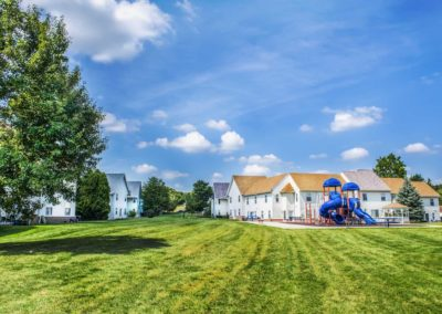 Exterior of Meetinghouse Apartments with grass and tree with playground