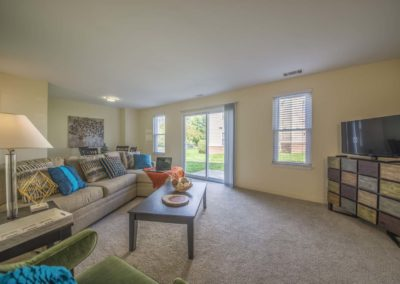 Spacious furnished living room with french sliding patio doors at Meetinghouse apartments