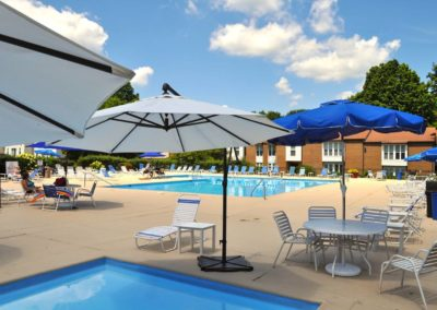Exclusive swimming pool with parasols and lounging chairs as community amenity for Boothwyn, PA apartment residents